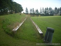 Läktarplatsen är imponerande. Två rader sittplatser hela långsidan och fint belägen i slänten österut. Måste ha varit en vacker syn när 2212 åskådare var här 1985! Att gräser växte högt vid mitt besök var väl bara tillfälligt då det var semestertider.