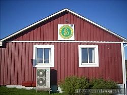 Här ses den stolta klubbstugan med klubbmärket på väggen och, mycket klokt, med en luftvärmepump för att hålla nere elkostnaderna.