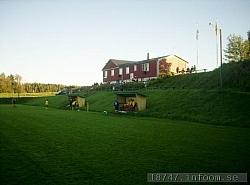 Som en riktig pampig villa ligger klubbstugan där uppe på höjden ovanför spelplanen. Avbytarbåsen syns i förgrunden.