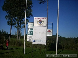 Här ses klubbmärket och den gamla klockan inramas av två flaggstänger. Några lokala sponsorers skyltarses också och som säkert fortsätter att stödja klubben.