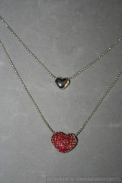 G17: Dubbelradigt halsband med ett hjärta med små röda swarovski stenar på...120:- SÅLD