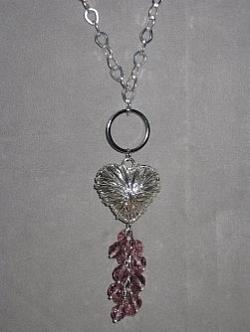 HA093 Ring heart: Långt halsband (ca 70cm) med trasselhjärta och klase med lila facetterade pärlor...Finns att köpa hos Studio MiniSÅLDFör att se en större bild, klicka på denna länk.