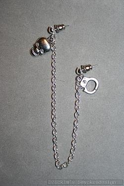 OR071 Death ear: Örhänge för två hål med döskalle och handfängsel...65:- SÅLD