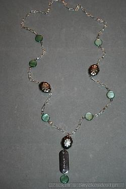HA160 Green love: Halsband (68 cm) med gröna snäckskalspärlor samt ett stansat hänge med texten