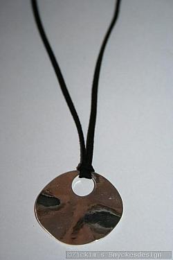 HA175 Silver wave: Halsband (40 cm lång) med mockaband med en rund vågig silverfärgad platta...89:-