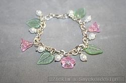AR195 Summer flowers: Rasselarmband med gröna glaslöv samt rosa glasblommor...89:- 49:-