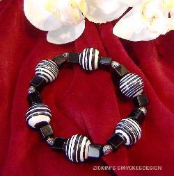 AR030 Candy corn: Armband med elastiskt band med stora randiga pärlor och svarta glas kuber...90:- SÅLD